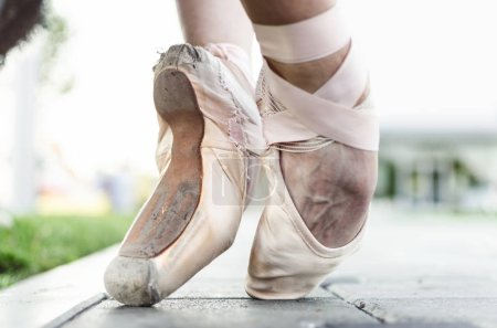 Close up of feet of young female classic ballet dancer in pointe shoes, posing in nature.