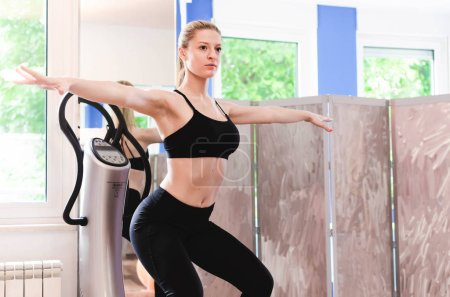 Beautiful young woman is working out at home on power plate.
