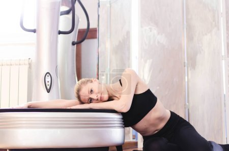 Photo for Young beautiful woman relaxing on power plate, indoors, space for text. - Royalty Free Image