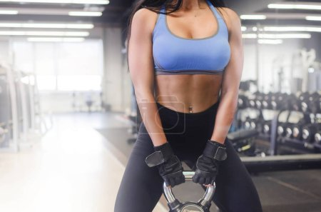 Cropped image of attractive woman doing deadlift with weights in a gym.