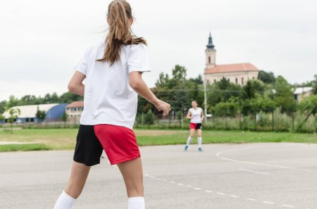 Young female handball players during the game on court.