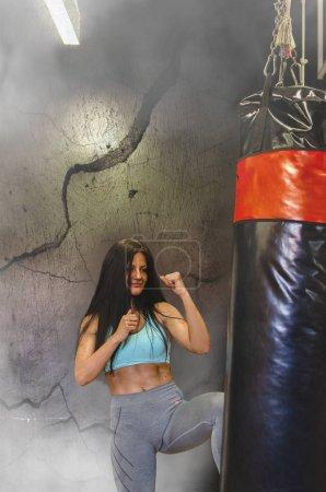 Photo pour Sac de boxe jeune femme attirante pour la boxe au gymnase - image libre de droit