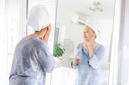Photo pour Belle femme senior, appliquer la crème anti-âge devant le miroir à la maison. - image libre de droit