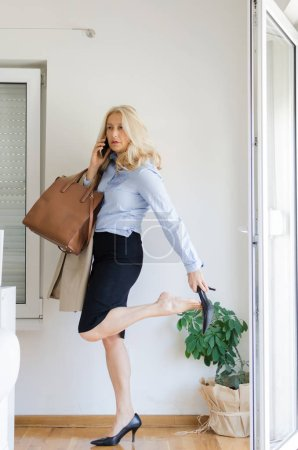 Photo for Portrait of senior woman taking shoes off after hard day at work. - Royalty Free Image