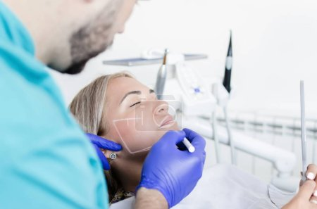 A male doctor works on tightening face to his patient. It uses the latest generation botox.