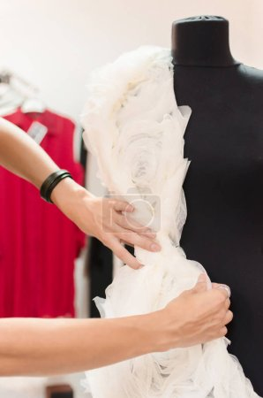 female tailor adjusting garment design on mannequin in workshop