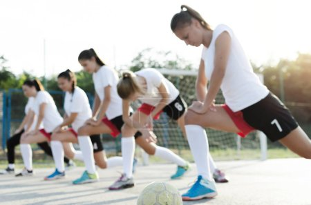 Blur image of young female players of handball doing stretching on ground.