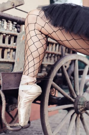 Vertical image of ballerina's feet, she's stepping up on an old horse carriage.