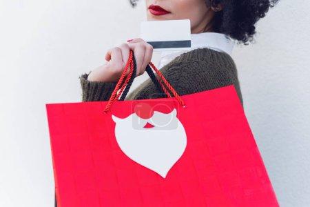 Gros plan de la jeune fille tenant la carte de crédit et des sacs à provisions à la main