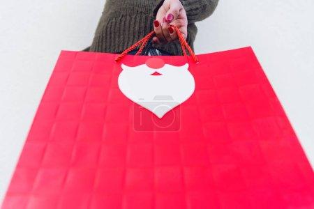 Photo pour Vue de dessous de femme tenant rouge sac shopping - image libre de droit