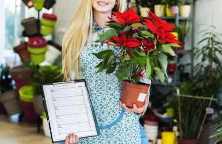 Photo pour Photo d'une vendeuse blonde souriante dans flowershop prendre les pré-commandes pour Valentine day et le 8 mars des acheteurs de rognée - image libre de droit