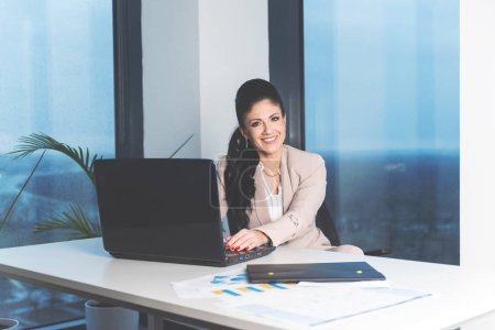 Selbstbewusste ehrgeizige Geschäftsfrau sitzt und posiert im Büro