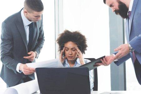 Photo pour Frustrée jeune femme d'affaires déprimée et ses collègues au bureau moderne - image libre de droit
