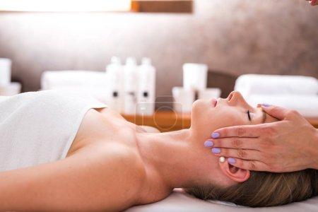 Photo pour Belle jeune femme relaxante avec massage du visage au spa de beauté. Bouteille, crème et huiles essentielles à l'arrière-plan - image libre de droit