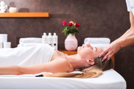 Photo pour Belle jeune femme relaxante avec massage de la tête au spa de beauté. Bouteille, crème et huiles essentielles en fond flou - image libre de droit