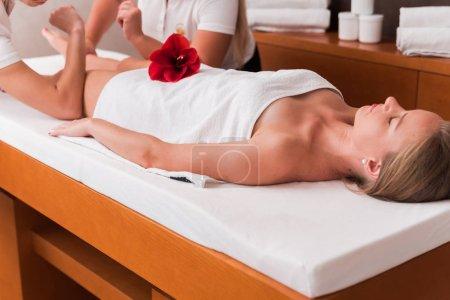 Photo pour Femme recevant un massage anticellulite des jambes dans le salon de spa. Décoration des fleurs. Deux masseurs en train de faire un massage royal des pieds - image libre de droit