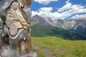 Puez Odle mountain range viewed from Mount Pic (above Raiser Pass) with a wooden religious carving in the foreground, Val Gardena, Dolomites, Italy