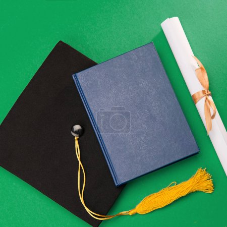 Top view of book, graduation mortarboard and diploma on green