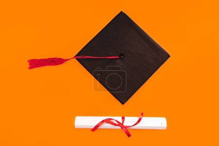 Top view of graduation mortarboard and diploma on yellow