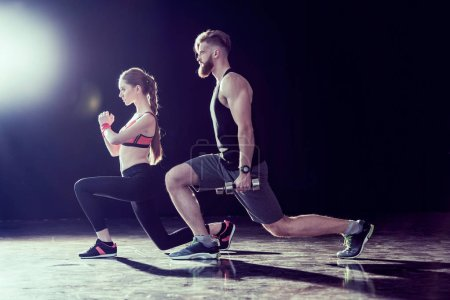 Side view of handsome sportsman and young fit woman training together on black