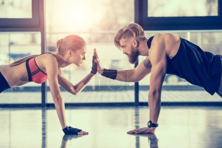 Photo for Side view of young sportsman and woman doing plank exercise and giving high five - Royalty Free Image