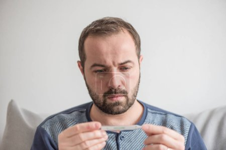 Photo pour L'homme malade vérifie la température corporelle avec un thermomètre au mercure. Thème des maladies virales, grippe, rhumes - image libre de droit