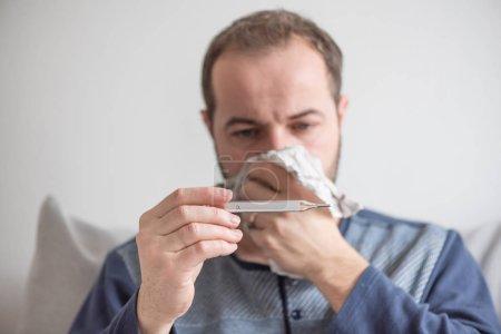 Photo pour Ill man vérifie la température corporelle avec un thermomètre au mercure. Thème des maladies virales, grippe, rhumes . - image libre de droit