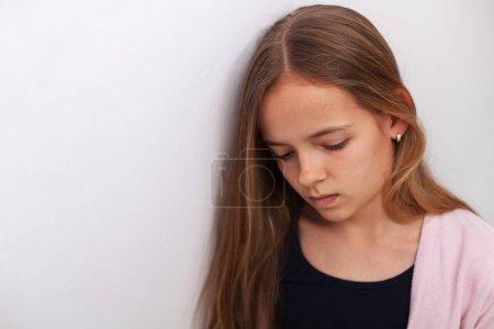 Photo pour Triste adolescente debout près du mur blanc avec les yeux abattus, pensant abot les énormes problèmes de l'adolescence - image libre de droit