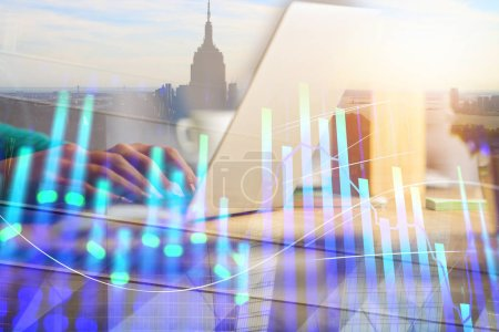 Hands using laptop with digital forex chart on abstract city background. Analytics and finance concept. Double exposure
