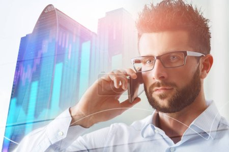 Portrait of handsome european businessman talking on the phone on abstract city background with forex chart. Communication and trade concept. Double exposure