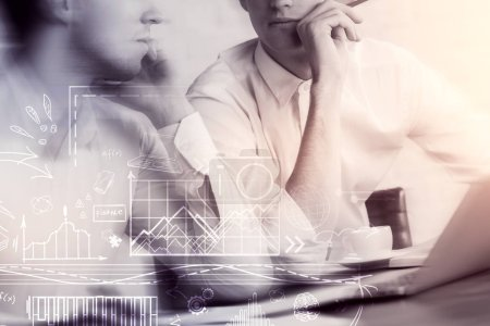 Two young businessmen using laptop with business sketch in abstract blurry toned office. Success and teamwork concept. Double exposure