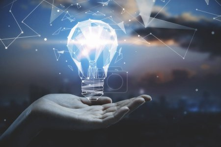 Photo for Business idea concept with hand holding 3d geometric light bulb at abstract city background - Royalty Free Image