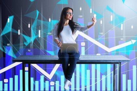 Photo pour Femme d'affaires heureuse assis sur la table avec ordinateur portable et smartphone faire selfie à fond de tableau financier - image libre de droit