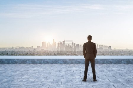 Back view of businessman on rooftop looking into the distance on city background with sunlight. Future concep