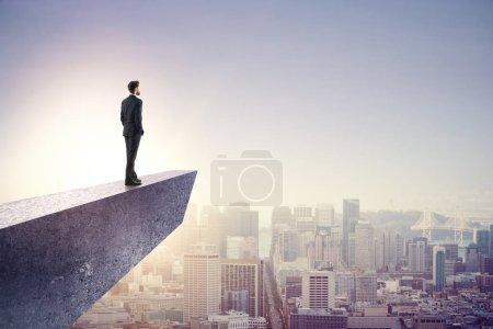 homme d'affaires, regardant au loin sur béton falaise surplombant la ville de la mégapole