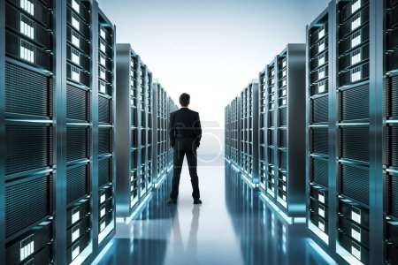 Back view of young businessman in shiny server room. Technology concept. 3D Rendering