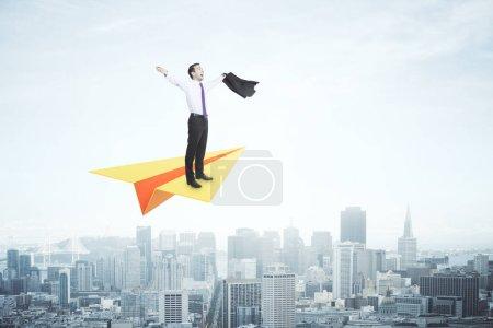 Businessman on paper plane celebrating success on city background. Leadership concept