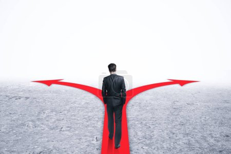 Businessman walking on arrows on abstract gray background. Different direction and path concept