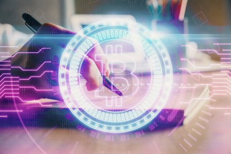 Photo for Cryptocurrency hologram, bitcoin, ico theme over hands taking notes background. Concept of blockchain. Multi exposure - Royalty Free Image