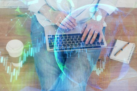 Photo for Double exposure of mans hands writing notes with laptop of stock market with forex graph background. Top View. Concept of research and trading. - Royalty Free Image