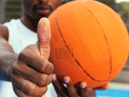Photo pour A man in a white T-shirt holds a basketball in front of him, shows everything ok with his hand. The concept of a healthy lifestyle. Selective focus, blurred image - image libre de droit