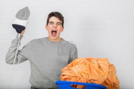 Photo pour Jeune homme avec des problèmes de repassage vêtements - image libre de droit