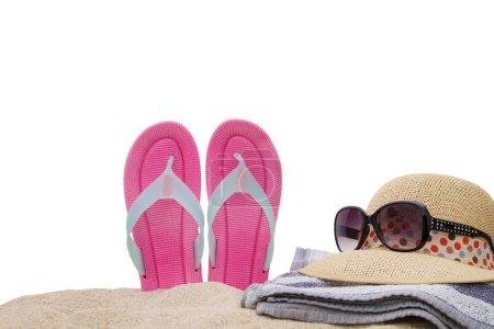 sombrero con gafas de sol y sandalias en la arena de la playa aislada