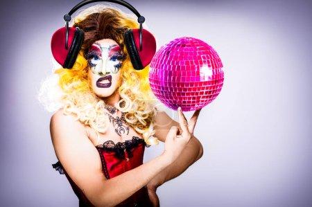 Photo pour Cool drag queen avec maquillage spectaculaire, look élégant glamour, posant avec fierté et style pour les droits des homosexuels l'égalité lgtb avec boule disco - image libre de droit