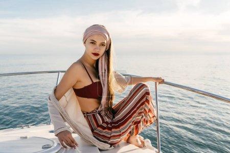 Photo pour Jeune belle fille en vêtements d'été élégants se trouve sur un yacht blanc, est allé sur un voyage en mer, en vacances - image libre de droit