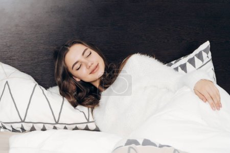 Photo for Cute sleepy girl in white pajamas lies in bed late at night, wants to sleep, tired, but smiles - Royalty Free Image