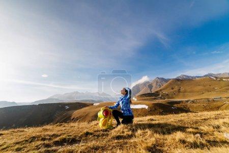 Photo pour Jeune fille active dans une veste bleue voyage à travers les montagnes du Caucase avec un sac à dos et une tente - image libre de droit