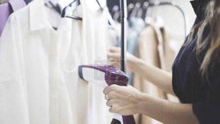 Photo pour Méconnaissable vendeuse jeune utilisant la vapeur pour repasser une chemise blanche dans un magasin de vêtements. Concept de la petite entreprise - image libre de droit