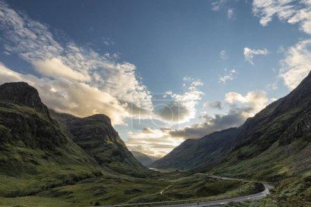 Photo pour Vue en fin d'après-midi de l'autoroute A82 serpentant à travers la vallée perdue, y compris les trois sœurs Beinn Fhada, Gearr Aonach et Aonach Dubh dans les Highlands écossais . - image libre de droit
