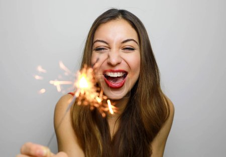 Smiling woman with burning sparkler in the studio shot